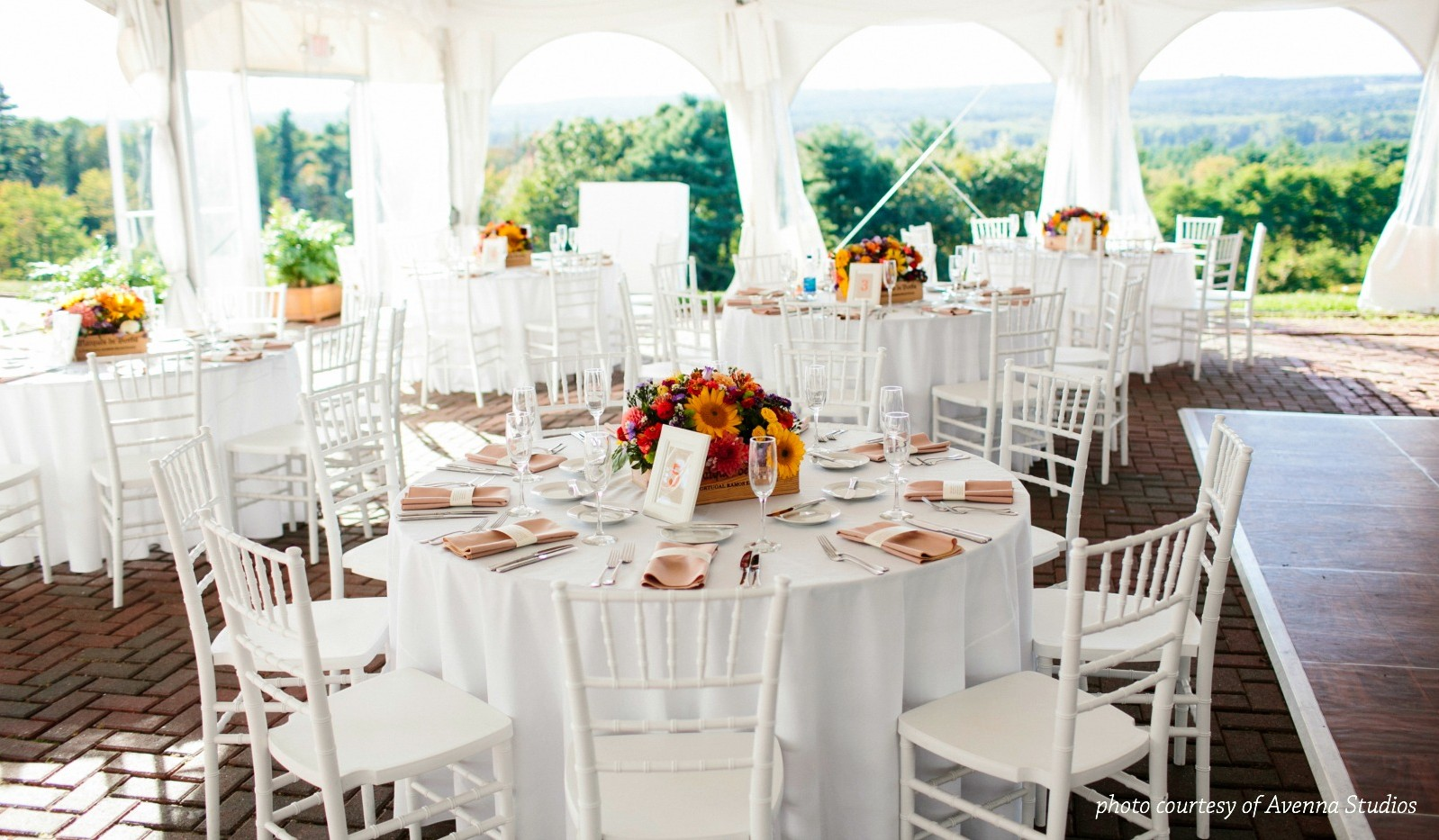 Dining room set for large event under tent with view of mountains and valley in background
