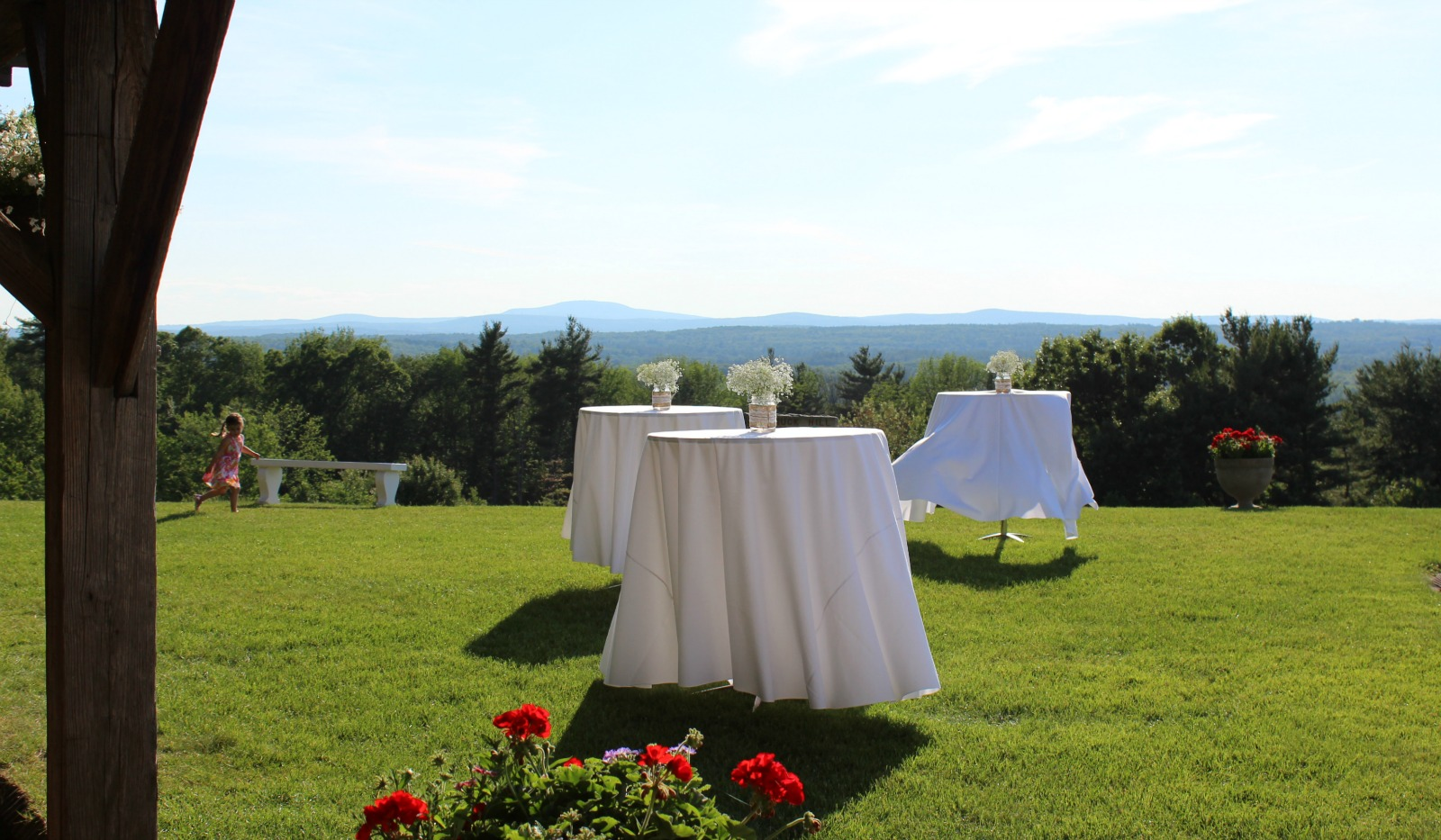 Cocktail tables set on lawn with mountains and Nashua river valley in background