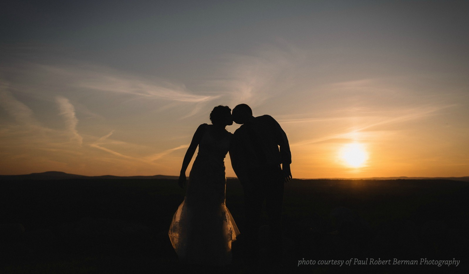 Bride and groom silhouette kissing with beautiful sunset in background