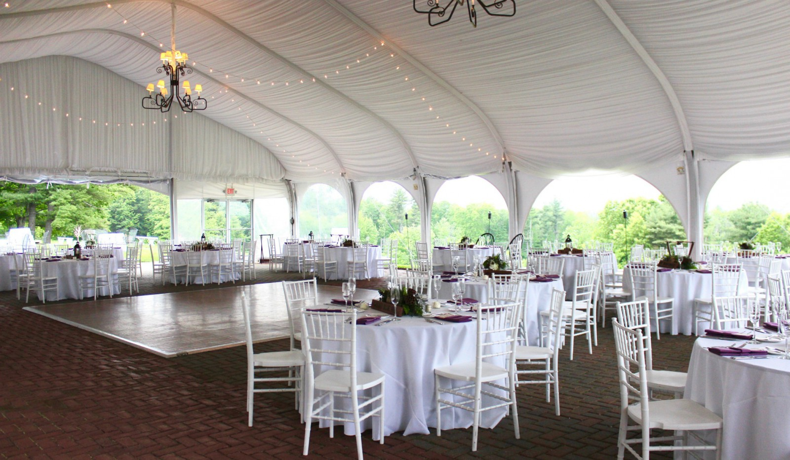 Dining room under tent with dance floor set for large event.