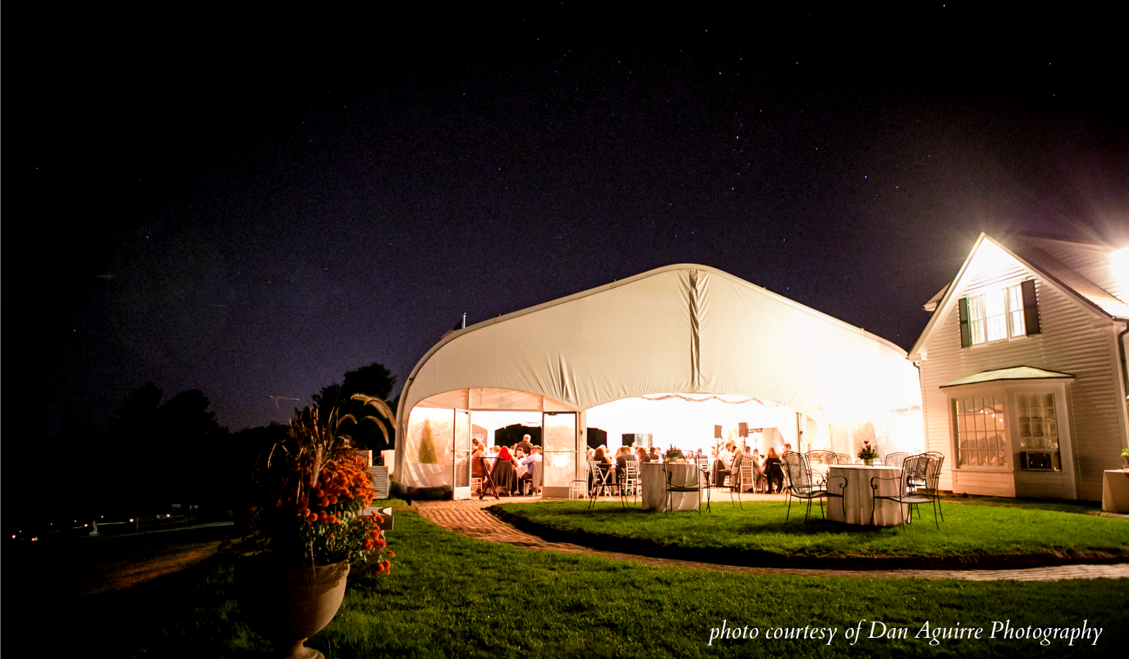 Large event in progress under tent at night, lit up.