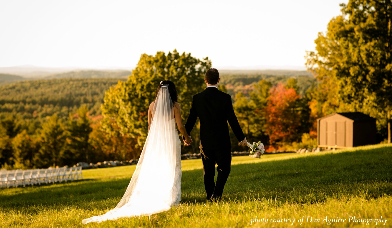 Bride and groom walking along lawn with view of mountains and valley in background